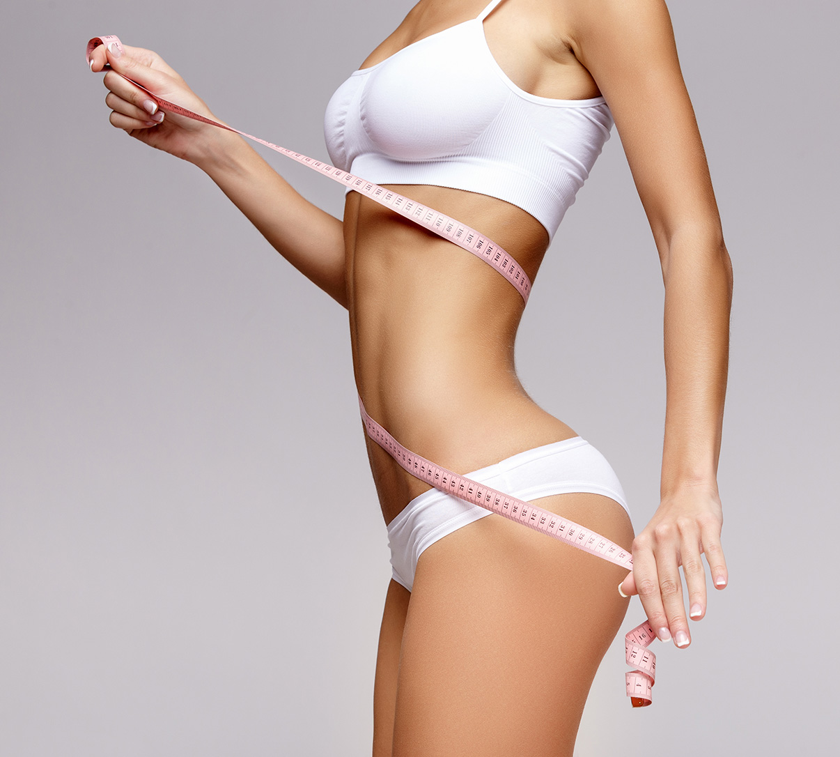 Side view of WarmSculpting model in white sports bra and panties with tape measure wrapped around her illustrating body sculpting success from Sculptique Aesthetics.