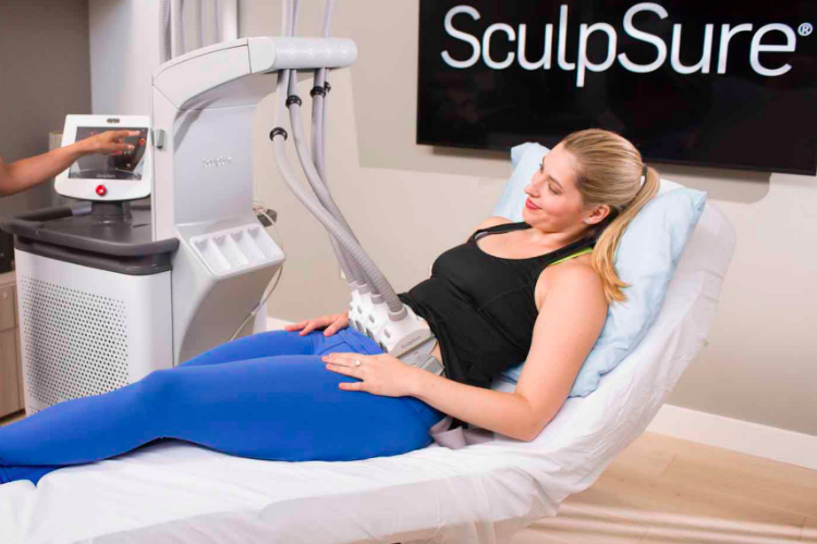 Woman in blue leggings and black sleeveless top getting SculpSure treatment.
